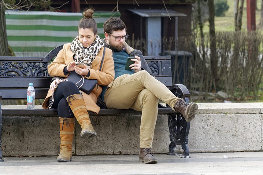 Couple both looking at their phones.